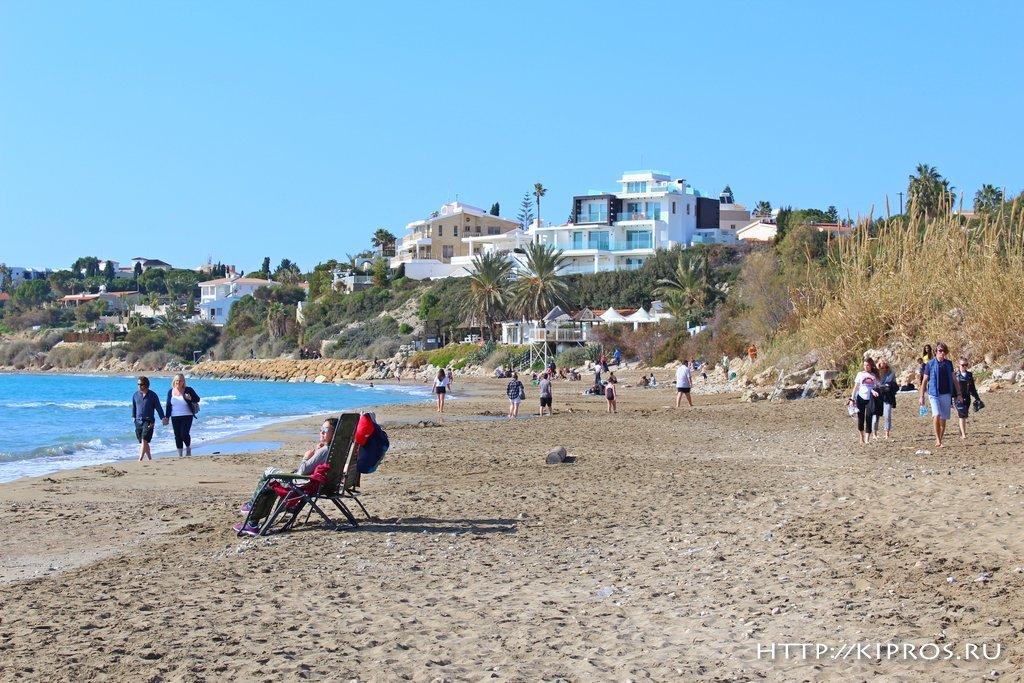 Туристы гуляют по пляжу на Кипре.